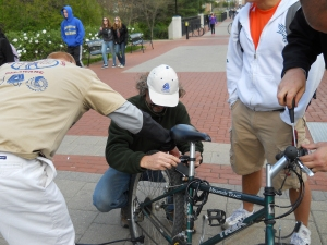 photo of partners pumping tires and installing lights for a UD student