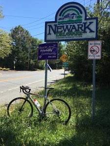 photo of bicycle under Newark, Delaware, and Bicycle Friendly Community signs