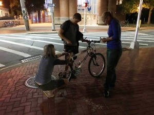 photo of BikeNewark members installing bike lights on a student's bike at night